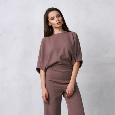 Young brunette woman with long straight hair wearing trendy short sleeved mauve jumpsuit and nude heeled shoes posing against white wall on background. Female model demonstrating fashionable outfit.