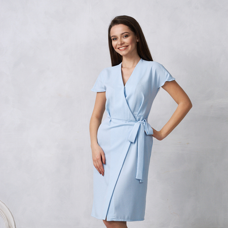 Attraktive Frau mit langen brünetten Haaren, gekleidet in modisches blaues Wickel-Midikleid mit kurzen Ärmeln, die lächeln und posieren. Lachendes weibliches Modell, das gegen weiße Wand auf Hintergrund steht.