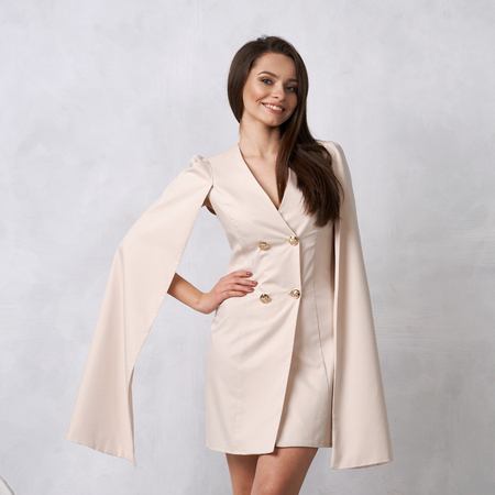 Attractive brunette female model wearing mini beige dress with golden buttons, split, long hanging sleeves and heeled shoes posing against white wall on background. Beautiful woman in trendy outfit.
