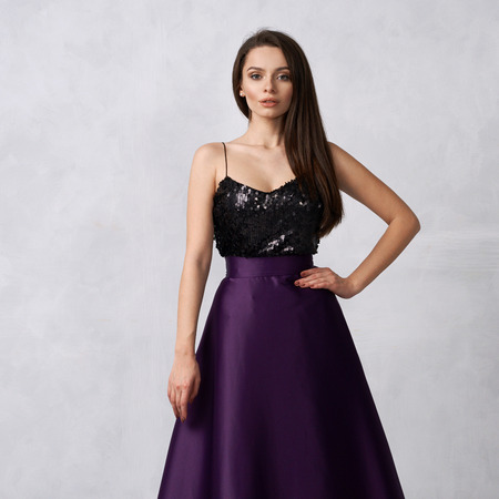 Charming brunette woman dressed in formal maxi dress with top decorated with black sequins and purple satin bottom. Female model posing in elegant evening gown against white wall on background. Stock Photo