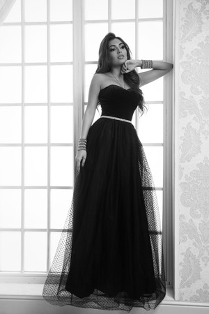 Beautiul tanned cacasian girl standing in black evening dress against window Фото со стока