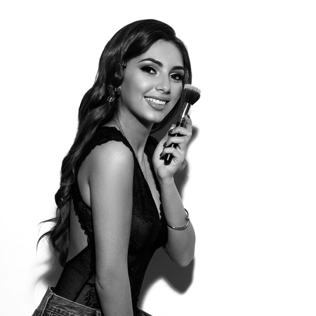 Young beautiful tanned woman in lave black bodysuit and blue jeans with long wavy brunette hair holding makeup brush and posing against white background