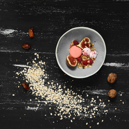Pink macaron, meringues, fig, raspberries, cereals in bowl standing on blue aged wooden table with ground oats and whole walnuts scattered around. Tasty morning meal, delicious sweet food. Top view. Zdjęcie Seryjne