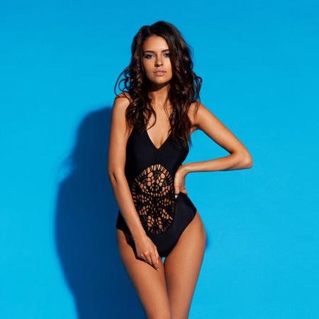 Junge schlanke gebräunte Frau im schwarzen Badeanzug, der gegen blauen Hintergrund aufwirft. Modeporträt des schönen Mädchens mit dem langen welligen brünetten Haar. Badebekleidung oder Bikinimodell Standard-Bild