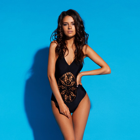 Young slim tanned woman in black swimsuit posing against blue background. Fashion portrait of beautiful girl with long wavy brunette hair. Swimwear or bikini model