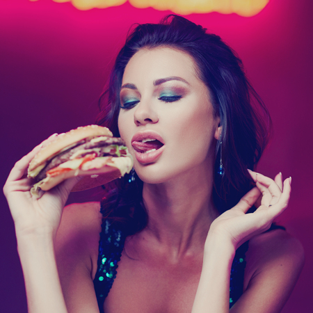 Sexy woman sitting at table in night club or bar and eating hamburger. Fashion style portrait Stock Photo