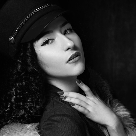 Stylish woman wearing green jacket dress and cap, fur coat and black jackboots posing in dark interior. Fashion style portrait. Brunette woman with curly hair. Close-up portrait.