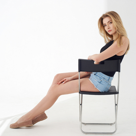 Young beautiful sexy woman in blue jeans shorts and black shirt posing and sitting on simple black chait in white studio. Fashion model with long straight hair. Stock Photo