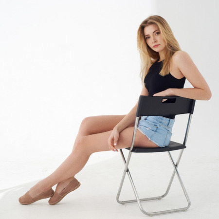 Young beautiful sexy woman in blue jeans shorts and black shirt posing and sitting on simple black chait in white studio. Fashion model with long straight hair. Zdjęcie Seryjne