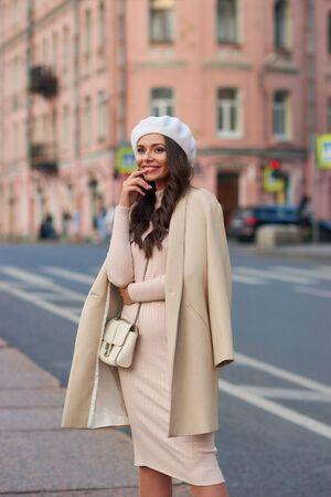 Joven mujer elegante muy hermosa en vestido rosa, sombrero de boina blanca y abrigo beige con bolso de cuero blanco de pie y posando en la calle de la ciudad. Aspecto de otoño con estilo de moda en colores pastel Foto de archivo