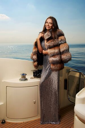 Young fashionable gorgeous glamorous woman in elegant silver shining evening dress and striped fur coat with long straight brown hair standing and posing at luxury yacht on a sunny summer day