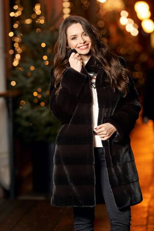 Cute pretty young woman in striped black and brown fur coat at city street. Beautiful girl walking at night
