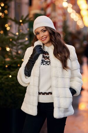 Outdoor portrait of young attractive happy smiling girl in white fur coat and knitten hat and gloves posing in street. Festive Christmas decorated city at background.