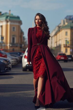 Young beautiful stunning woman in red luxury evening dress with flying hem walking city street on a sunny evening. Elegant lady with makeup and wavy brunette hair. Full length fashion portrait