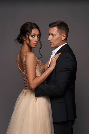 Attractive beautiful and well-dressed young adult couple posing in studio on gray background. Woman in beautiful evening dress and man wearing black classical suit with white jacket Stockfoto