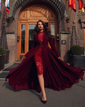 Young beautiful stunning woman in red luxury evening dress with flying hem walking city street on a sunny evening. Elegant lady with makeup and wavy brunette hair. Full length fashion portrait Reklamní fotografie