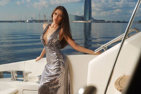 Gorgeous woman with long straight brown hair in silver shining dress sitting at white sofa at luxury yacht on a sunny summer day. Water and blue sky at background