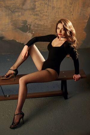 Ritratto di stile di moda a figura intera. Donna castana sexy in corpo nero e collant a rete. Bella ragazza con i capelli ricci seduto al banco in palestra grunge. Stile anni '90 Archivio Fotografico