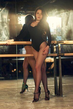 Ritratto in stile moda anni '90. Donna sexy in body nero, collant a griglia, tacchi alti che ballano in classe usando la sosta. Ragazza sensuale con lunghi capelli mossi