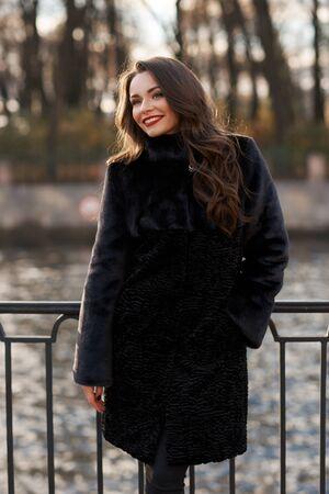 Hübsche lächelnde Frau im kurzen schwarzen Pelzmantel, der am Flussdamm in der Stadt steht