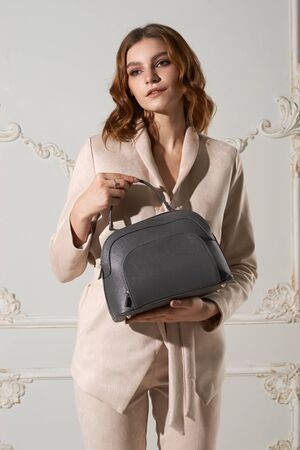 Body length studio portrait of young business woman with red wavy hair in beige suit and high heel shoes holding gray handbag and standing against wall. Fashion style shoot
