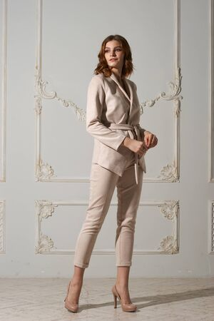 Full length studio portrait of young business woman with red wavy hair in beige suit and high heel shoes standing against wall 版權商用圖片