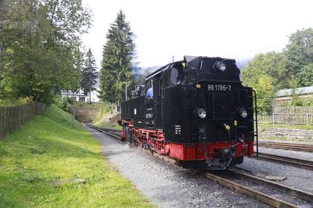 narrow gauge: BROCKEN MOUNTAIN, SAXONY-ANHALT GERMANY May 26 2012: historical locomotive is going up high to Brocken Peak with tourists. Brocken is part of Harz National Park.