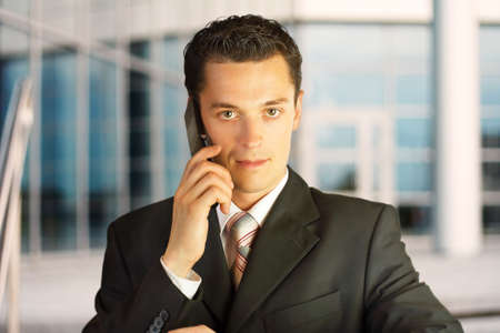 Close-up portrait. Businessman outside a modern building with phone. photo