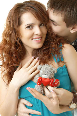 Young attractive happy smiling couple isolated on white with teddy bear photo