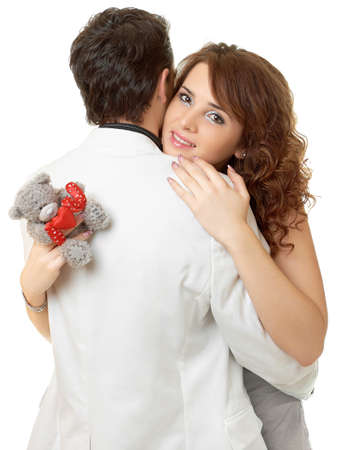 Close-up portrait of attractive couple flirting isolated on white with teddy bear photo
