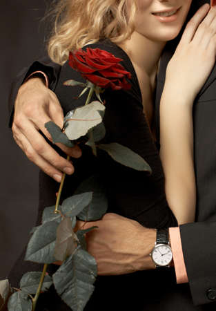 women hugging: Beatiful couple in love with rose on black background Stock Photo