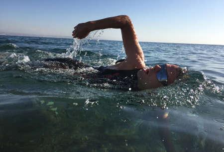 Professional triathlete practicing in open water. Swimming in sea. Triathlon training in wetsuit.