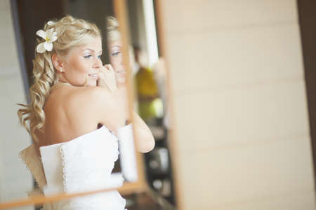 necklase: Gorgerous bride standing in front of mirror and fixing her hair and make up. Putting earings, powdering and smilling.