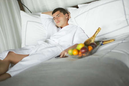 likable: Gorgeous young man, gentleman lying on a bed at the hotel. Wake up call and getting ready.
