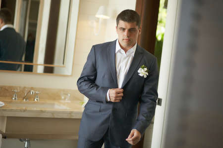 cuffs: Handsome and strong man putting on official suit. Nice and slender groom wearing wedding suit and putting on cuffs in bedroom looking in mirror.