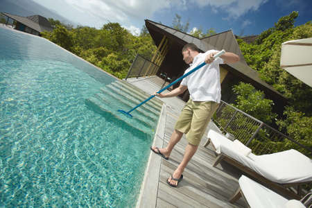 hotel resort: Swimming pool cleaner during his work at tropical villa. Professional cleaning service at work. Private property service.