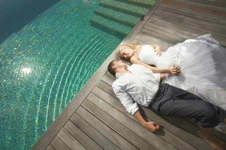 Belle jeune couple allongé près de la piscine avant le mariage. chaude journée d'été, les préparatifs de mariage à l'île tropicale des Caraïbes ou à Hawaii. Banque d'images - 56745522