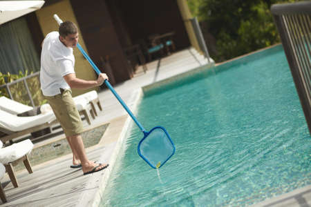 Swimming pool cleaner during his work at tropical villa. Professional cleaning service at work. Private property service.