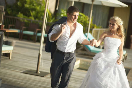 suntanned: Lovely bride and groom coming across pool area after wedding. Warm summer day, wedding at tropical caribbean island or Hawaii. Stock Photo