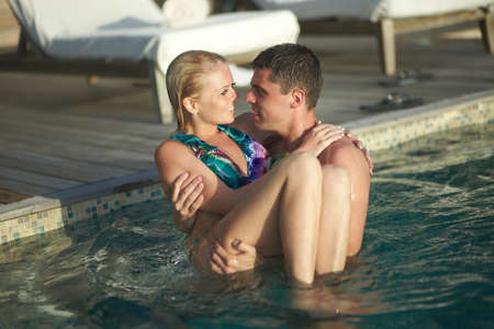 carrying girlfriend: Handsome young man carrying girlfriend from pool in sexual embrace. Beautiful blondy model and slender boy. Stock Photo