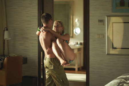 carrying girlfriend: Handsome young man carrying girlfriend from pool to bedroom in sexual embrace. Beautiful blondy model and slender boy.