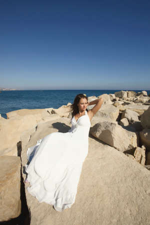 marvelous: Divine, gorgeous bride standing and posing on the rocks and stones under summer sun. Marvelous white dress and windy flying cloth.