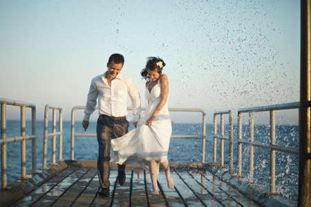 happy wedding: Gorgeous wedding couple running through the spray, splashes and drops on sunset. Beautiful wooden old pier pacific or atlantic ocean. Stock Photo