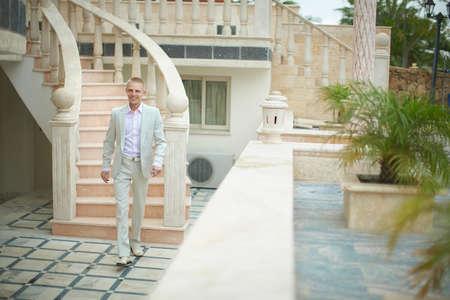 tenacious: Handsome, blondy, happy groom walking to brides room across terrace. Stock Photo