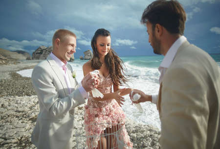 preacher: Young, sexy and attractive couple listening preacher speech during gorgeous ceremony on sandy beach.  Dream destination wedding, caribbean or Hawaii. Stock Photo