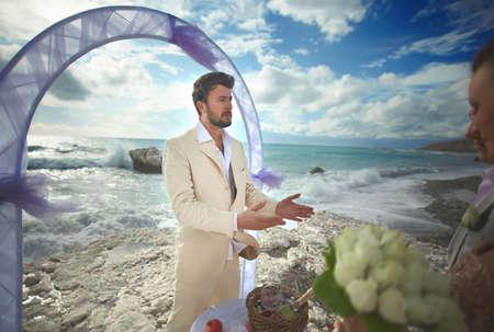predicador: Young, sexy and attractive couple listening preacher speech during gorgeous ceremony on sandy beach.  Dream destination wedding, caribbean or Hawaii. Foto de archivo