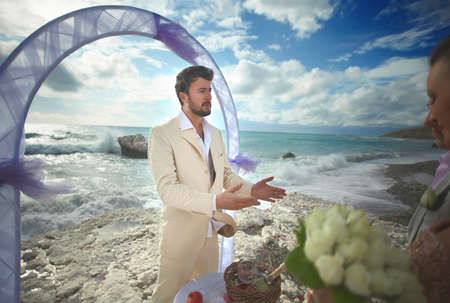 Young, sexy and attractive couple listening preacher speech during gorgeous ceremony on sandy beach.  Dream destination wedding, caribbean or Hawaii. Stock Photo