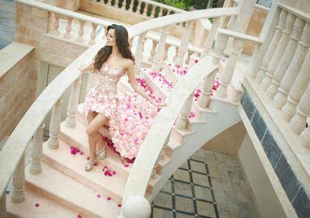 bajando escaleras: Dream wedding, beautiful bride, walking down stairs in flawless dress with flowers behind.