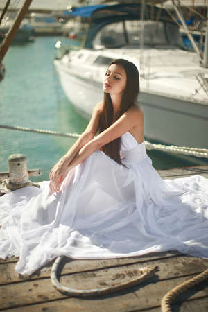 fashion magazine: Beautiful, glamorous woman, girl sitting at pier in yacht club near sail boats. Fashion, magazine picture.