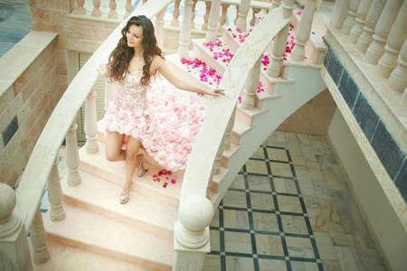 down stairs: Sueño de la boda, la novia hermosa, caminando por las escaleras en el vestido impecable con flores detrás.